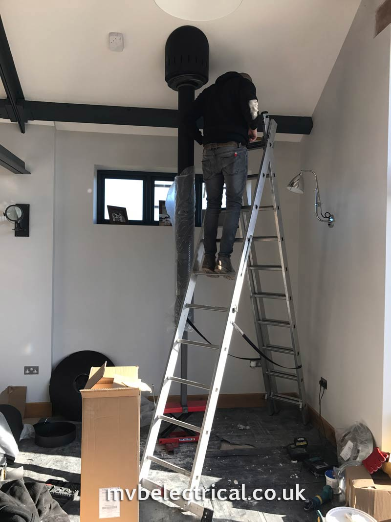 Hanging fireplace being fitted - workman on ladder to roof